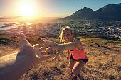 Young woman reaching mountain top, sunrise