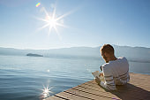 Young man relaxing on lake pier, reads book