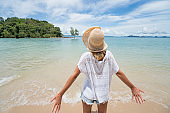 Young woman arms outstretched on tropical beach, vacations concept