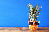 Pineapple with sunglasses on the table. Beach and tropical theme.