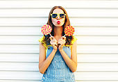 Fashion young woman holding a lollipops and blowing her lips over a white background