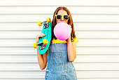 Fashion woman blowing a pink air balloon having fun over a white background