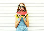 Happy smiling young woman holding a watermelon over a white background
