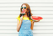 Fashion pretty woman eating a slice of watermelon in the form of ice cream over a white background