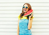 Fashion smiling young woman holding slice of watermelon in hands on a white background