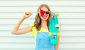 Fashion pretty smiling woman with a slice of watermelon ice cream skateboard on a white
