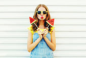 Fashion pretty cool girl with a two slice of watermelon ice cream blowing her lips over a white background