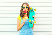 Fashion pretty cool girl eating a slice of watermelon ice cream holds a skateboard on a white