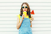 Fashion portrait pretty cool girl drinks a juice from cup holds slice watermelon ice cream over a white