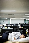 A businessman sleeping at a company