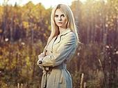 Portrait of young beautiful woman in autumn cloak