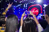 Young woman taking photos with smart phone at music festival