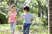 Happy children holding hands running in woods