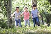 Happy children racing in woods