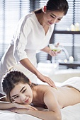 Young woman receiving back massage at spa center