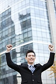 A businessman outside office buildings with his arms raised in celebration