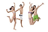 Young men and young women in swimsuit jumping in mid-air