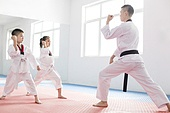 Young instructor teaching children Tae Kwon Do