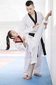 Young instructor teaching girl Tae Kwon Do