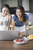 Best female friends using laptop for online recipe