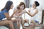 Best female friends applying make-up at home