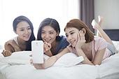Best female friends taking self portrait on bed