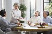 Happy senior friends eating together