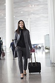 Businesswoman pulling wheeled luggage in airport lobby