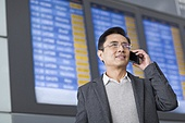 Businessman talking on cell phone in airport
