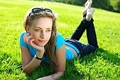 Girl laying on fresh green grass