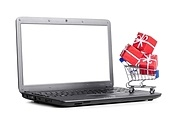red gift boxes in shopping cart on a laptop, cut out from white