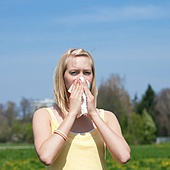 Woman with a flu or an allergy sneezing into her handkerchief in spring