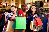 Group of three women - white, black and Asian  shopping downtown in a mall