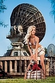 A pretty sexy blonde with a pocket dog in a bag in front of radar station.