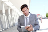 Businessman using electronic tablet outside a building