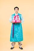 A Korean man in a hanbok holding a gift box