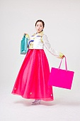A Korean woman wearing a hanbok with a shopping bag