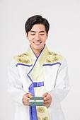 A Korean man in a hanbok holding a gift card