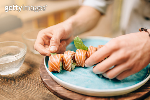 Male chef cooking sushi rolls