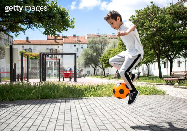 Boy play with football ball
