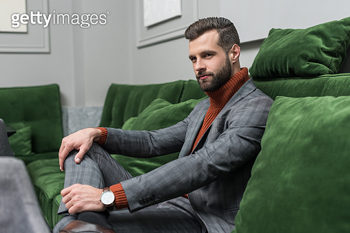 Man sitting on green sofa