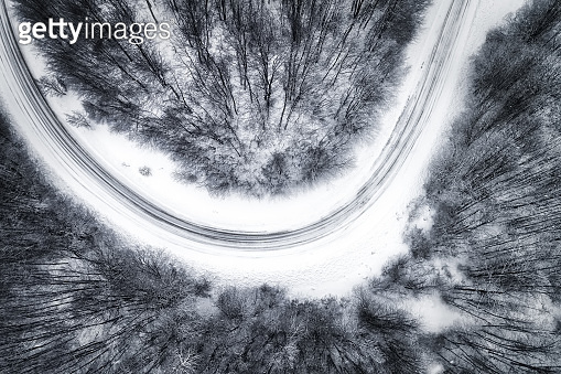 Aerial view of snowy forest with a road