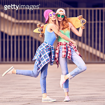 Two Young Girl Friend on Skateboard