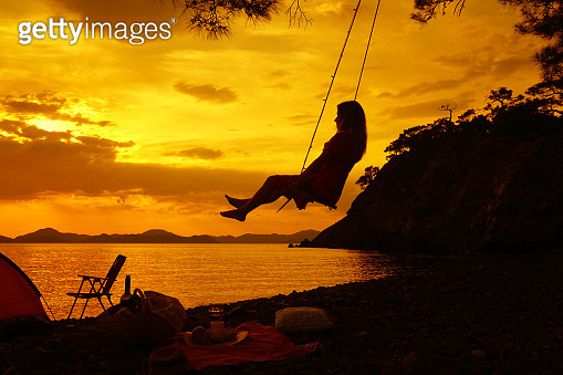 Girl on the swing at sunset