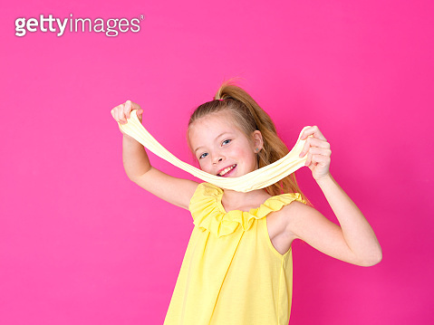 Girl is playing with yellow slime