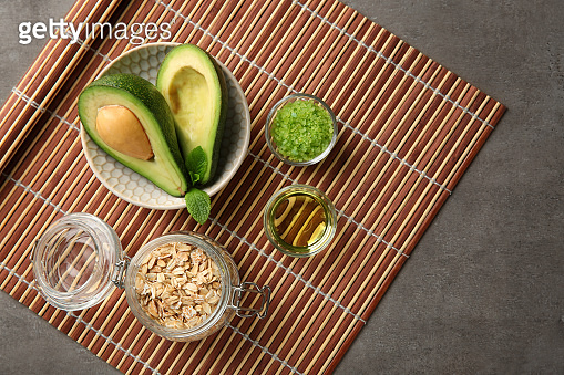 Avocado with ingredients for natural homemade cosmetics on bamboo