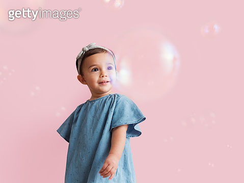 Small child looking at floating bubbles