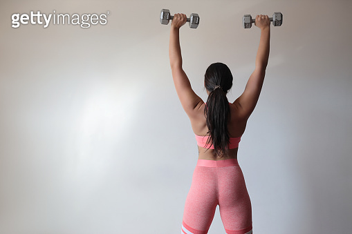 Young Woman Using Dumbells