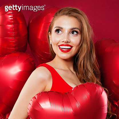 Pretty surprised woman holding red balloons