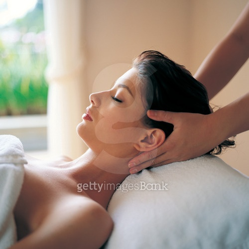Side profile of a young woman getting a massage